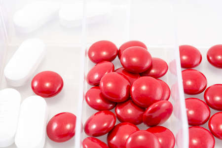 Close up Red and white pills in box on a white background Stock Photo