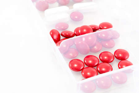 Red and white pills in box on a white background