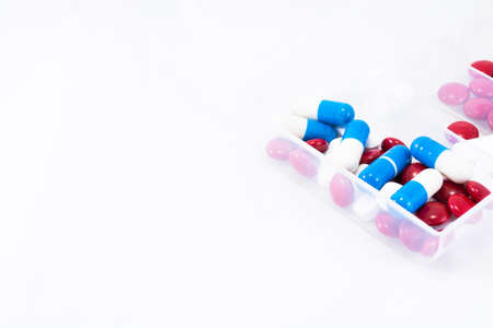 Red, blue and white pills in box on a white background