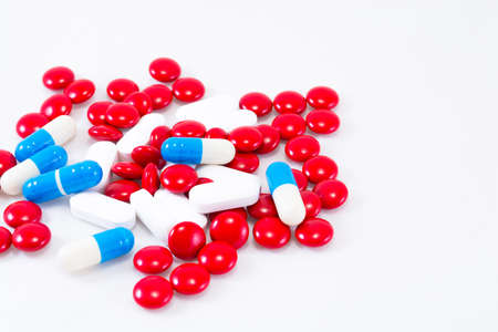 Red, blue and white pills on a white background