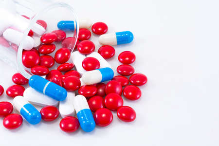 Red, blue and white pills in small cup on a white background