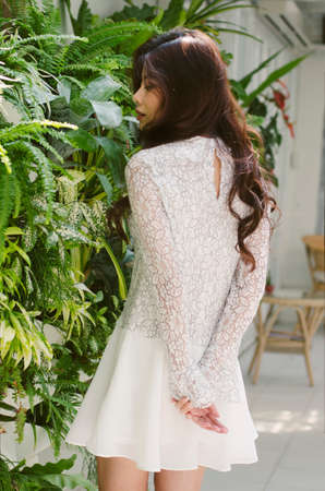 greenery: A lady in front of greenery plant wall