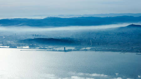 Foggy morning in Barcelona viewed from aircraft window  photo