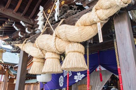 enclosing: Corda di paglia di riso utilizzato per la purificazione nella religione scintoista giapponese. (Santuario di Kushida Fukuoka, Giappone) Editoriali