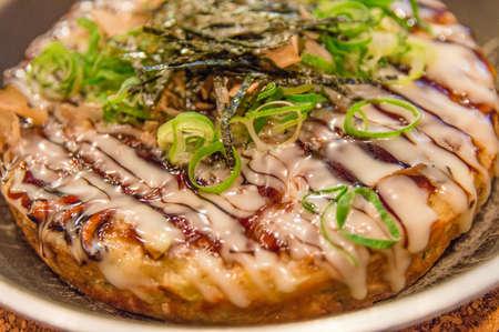 Okonomiyaki is a Japanese style meat and vegetable pancake. photo