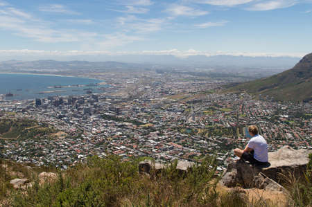 robben island: A man enjoying the scenics of Cape Town, South Africa, On top of the Lions Head Mountain. Stock Photo