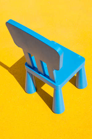 Blue Kids Chair on Yellow Background photo