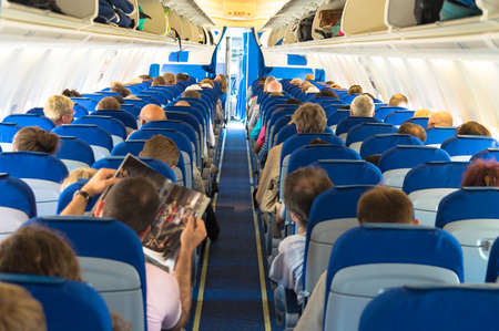 Airplane aisle with group of passengers Фото со стока