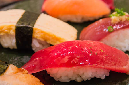 Assorted sushi on black dish photo