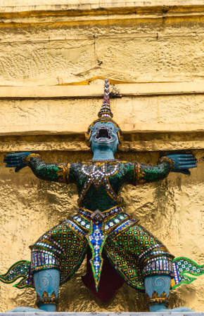 Yaksha supporting golden chedi statue on Grand Palace, Temple of the Emerald Buddha Wat Phra Kaeo, Bangkok, Thailand. photo