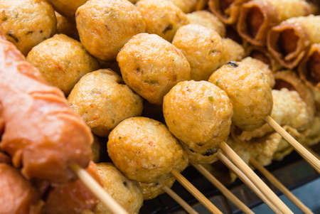 Fishballs and sausages on bamboo sticks sold on street market in bangkok, thailand.