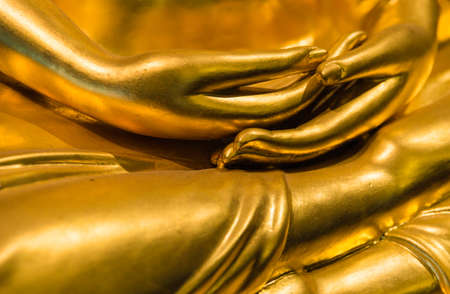 Close up hands of golden buddha photo