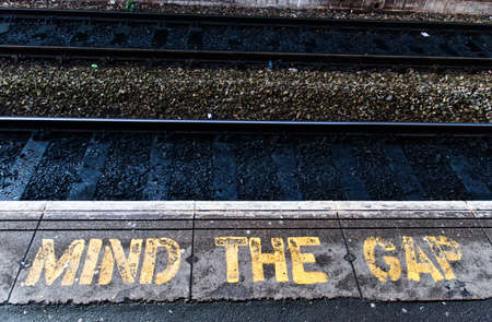 western script: Train platform edge. Painted warning on the floor. Stock Photo