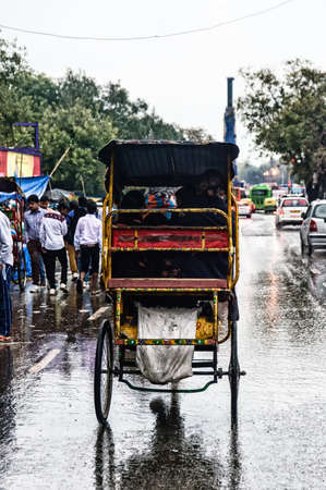 increasingly: New Dehli, India - 1 marzo 2015: ciclo risci� e un passeggero cerca di farsi strada, nonostante la pioggia e il livello dell'acqua in aumento sempre pi� rischioso.