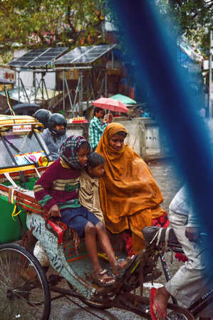 New Dehli, India - March 01, 2015: cycle rickshaw and a passenger try to make headway, despite the heavy rain and the increasingly risky rising water level.