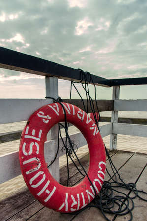 A life buoy hung on a dock overlooking a large body of water. photo
