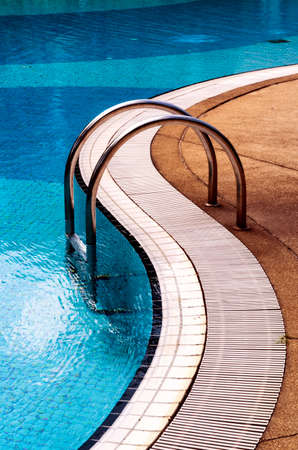 Curved poolside of a fresh blue swimming pool with stairs. The pool steps are in line with the curve of the pool.