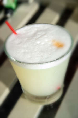 Peruvian cocktail named Pisco Sour made of Pisco (Peruvian grape schnaps),lime juice, syrup, egg white, and angostura (bitter fluid) drops on top (Selective Focus, Focus on the front of the angostura) photo