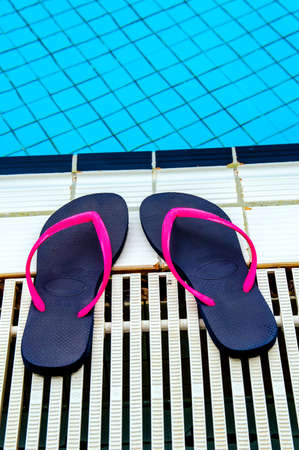 striping: Pair of sandals on the poolside. flip flops have a pink striping. The pool has fresh blue water. Editorial