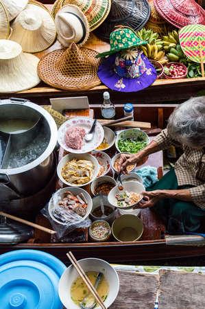 multi national: Food vendor at the Damnoen Saduak Floating Market preparing Thai style food Thailand. Stock Photo