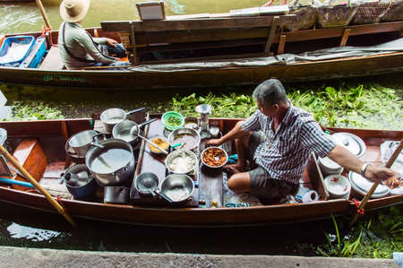 saduak: Food vendor at the Damnoen Saduak Floating Market preparing Thai style food Thailand. Editorial