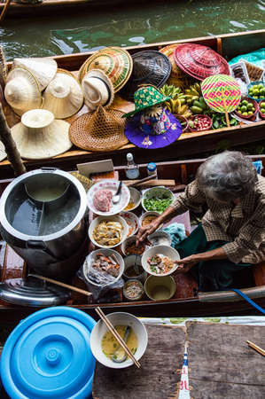 thailand: Food vendor at the Damnoen Saduak Floating Market preparing Thai style food Thailand. Stock Photo