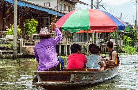 RATCHABURITHAILANDJUNE 19 : Unidentified People and Tourist on the boat tour Damneonsaduak Floating Market on June 19 2015 in RatchaburiThailand.