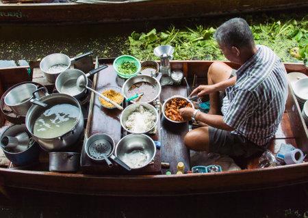 multi national: Food vendor at the Damnoen Saduak Floating Market preparing Thai style food Thailand. Editorial