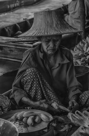 RATCHABURI THAILAND  JUN 19: A woman makes Thai food at Damnoen Saduak floating market on June 19 2015 in Ratchaburi Thailand. Its popular for traditional style Thai food and old Thai culture.