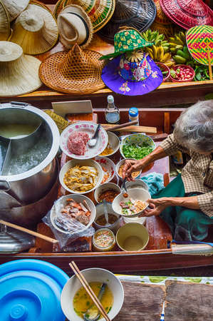 thai chili pepper: Food vendor at the Damnoen Saduak Floating Market preparing Thai style food Thailand. Stock Photo