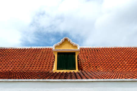 dormer: Symmetrical yellow rooftop dormer with green window shutters and red roof tiles in the caribbean.