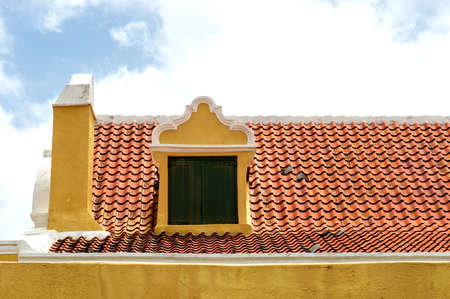 red shutters: Symmetrical yellow rooftop dormer with green window shutters and red roof tiles in the caribbean.