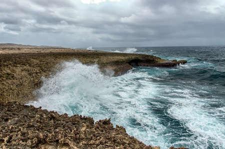 boka: Splashing waves at a rough and rocky coastline at Boka Pistol. This is the northern coastline at Shete Boka national park at Curacao, Dutch Antilles.