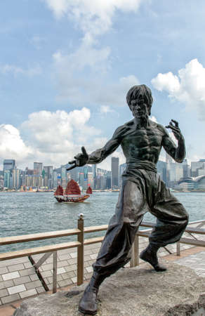 Hong Kong, China - January 20, 2013: People visiting a statue of the martial arts expert and film star Bruce Lee (1940 - 1973). The statue was unveiled in 2005 on the Avenue of Stars, along the Tsim Sha Tsui waterfront. Редакционное