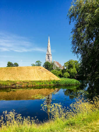 churchill: St. Albans Church is located in Churchill Park, or Parken if youre Danish, and rises over the canal and levee of the park Stock Photo