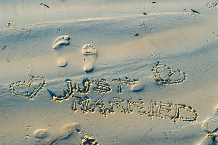 short phrase: Just Married written in the sand Stock Photo