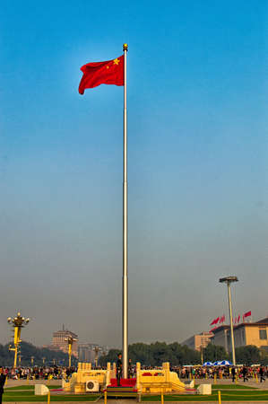 Beijing, China - October 4th 2015 The Chinese flag flies proudly in Tiananmen Square whilst tourist mill about taking photographs Редакционное