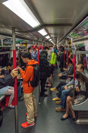 unsustainable: Hong Kong, China - November 30, 2015: Businessman with smartphone inside subway train in Hong Kong.With over 150 stations, four million people use it every week. This very efficient system created in 1979 has relieved the unsustainable traffic growth in o