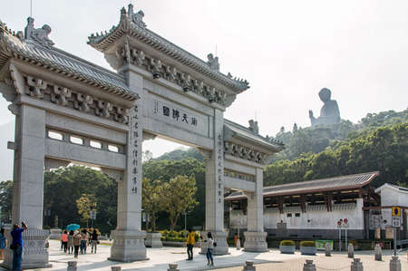 future buddha: Tourists sightseeing the Po Lin Monastery, surrounded by the giant Tian Tan Buddha statue, located on Ngong Ping Plateau on Lantau Island, Hong Kong. The main temple houses three bronze statues of the Buddha – representing his past, present and future l