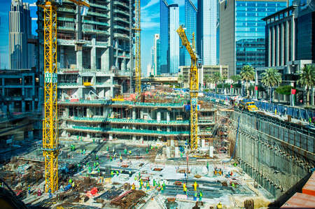 construction machinery: Dubai, United Arab Emirates - March 25, 2015: Massive buiding site with a lot of building machinery and many foreign construction workers in Dubai near by Burj Khalifa. Picture showing economical growth of UAE.