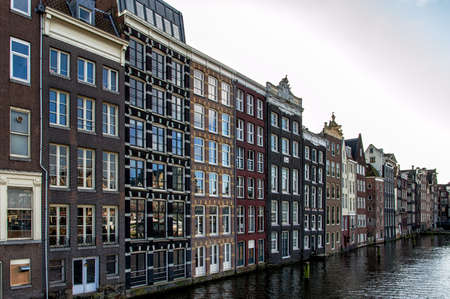 amstel river: Amsterdam City Scene. Visible are many typical dutch houses. Old 17th and 18th century brick houses along a canal in center of Amsterdam, Netherlands. Stock Photo
