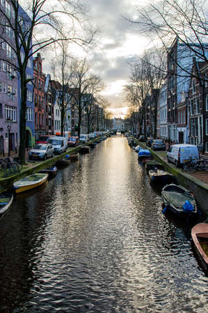westerkerk: This is a landscape image of a canal in Amsterdam, Netherlands. Several boats along the water are visible within the shot. Editorial