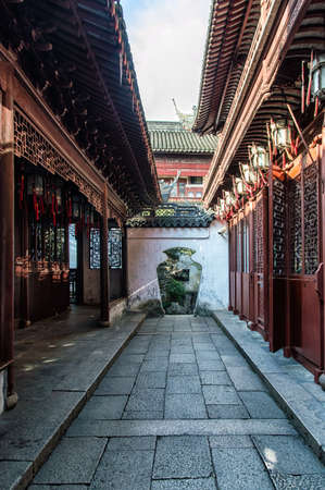 white washed: Curved arch over flagstones through white washed wall traditional Chinese architecture of red wooden screens, lanterns and pagoda tile roofs in the tranquil retreat of Yuyuan Gardens in the heart of Shanghai, China.
