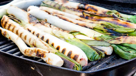 calsotada: a pile of calçots, typical catalan sweet onions, on the barbecue