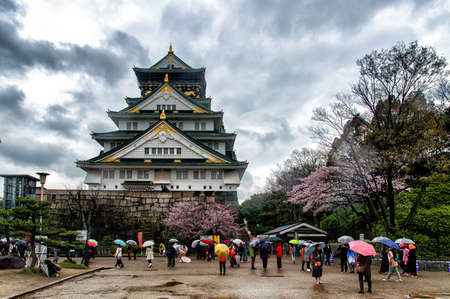 castle district: Osaka, Japan - April 01, 2016: Crowds of tourists visiting Osaka Castle Park beneath the iconic five storey keep in the heart of Japans vibrant second city. Editorial