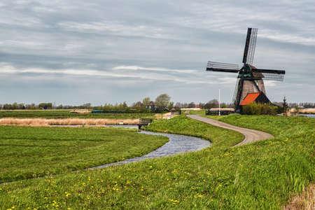 polder: Dutch Windmill along a small canal in polder Schermer, Netherlands Stock Photo