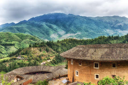 Traditional earthen Tulou Chinese huts, a landmark tourist attraction from the Fujian province of China. These large round huts are still being lived in today by the Hakka people. Stock Photo