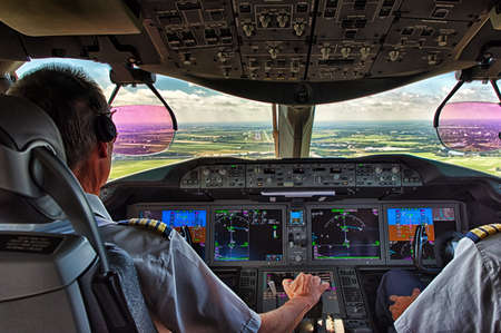 Pilot and copilot in commercial plane in cockpit, Pilot operation with control panel.