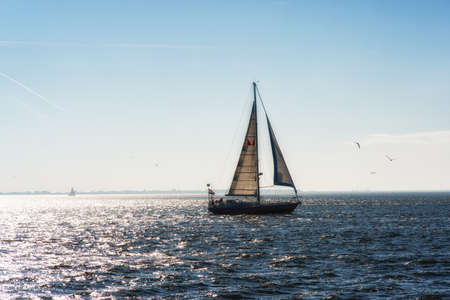 spinnaker: Sailing boat on the open sea at the sunset Stock Photo