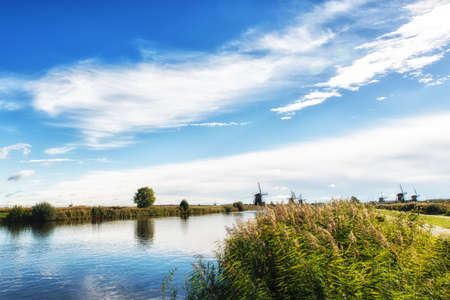 dutch: Dutch landscape with a canal and grass fields with mirror reflection of clouds in water Dutch canal and grass Landscape Stock Photo
